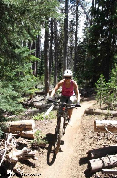 Riding in Bend with a dialed out DEVINCI bike from the shop bike left  Jillian Raymond with nothing left to do but smile, smile, smile.